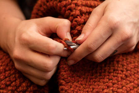 purl: Young woman knitting a scarf with maroon yarn. Stock Photo