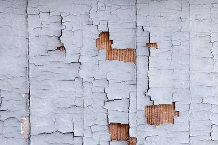 aged wood: Distressed building wall with white aged paint chipping off Stock Photo