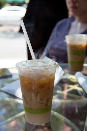 slurp: Iced coffee on a table at a coffee house with morning paper and fresh air