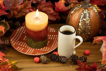 A cup of coffee with a lit candle and pumpkin decoration as a fall table setting