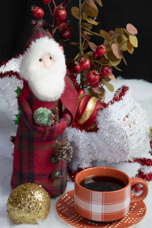 Home decor Santa and his sleigh on snow and tree decorations table setting accompanied by a warm cup of coffee