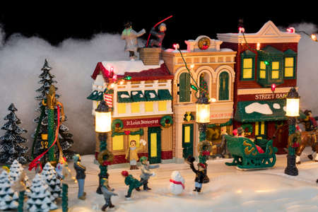 Miniature Christmas village scene with houses, trees, people, dogs and cats celebrating the holidays