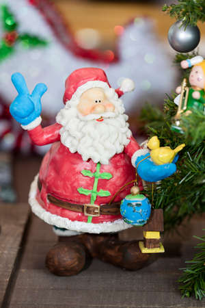 kris kringle: Brightly colored Santa Claus ornament holding presents next to a Christmas Tree
