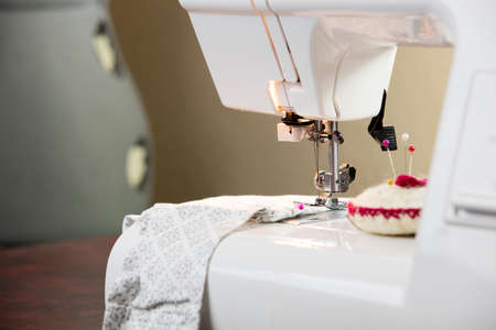 darn: White sewing machine and accessorized by pins and fabric