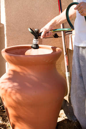 pot hole: A man preparing a clay pot for a garden by creating a hole and base in ground, then filling and planting with garden soil and water.