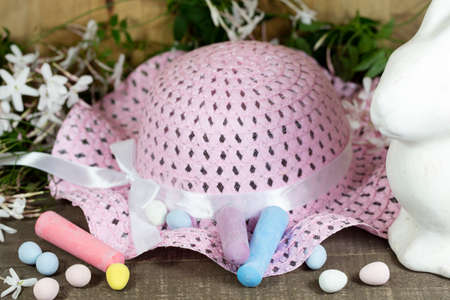 hard love: White Easter Bunny sitting with colored eggs in a nest of Jasmines, chalk and candy eggs and pink hat