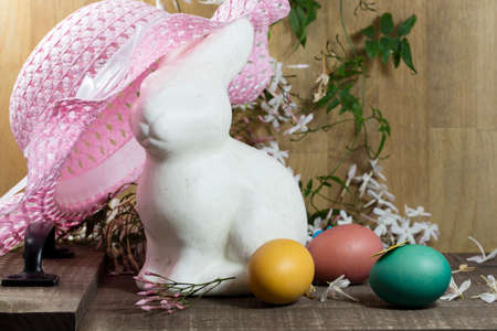 pink hat: White Easter Bunny sitting with colored eggs in a nest of Jasmines and pink hat