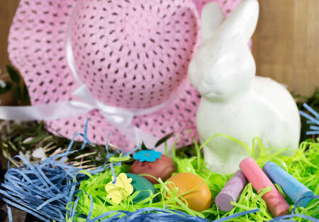 pink hat: White Easter Bunny sitting with colored eggs in a nest of Jasmines, chalk and pink hat Stock Photo