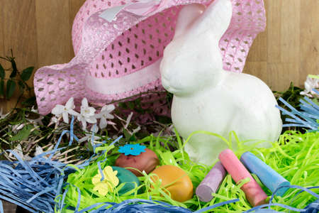 hard love: White Easter Bunny sitting with colored eggs in a nest of Jasmines, chalk and pink hat Stock Photo