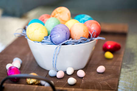 Colored orange, purple, yellow, red and greed Easter eggs in a bowl with candy on the table top