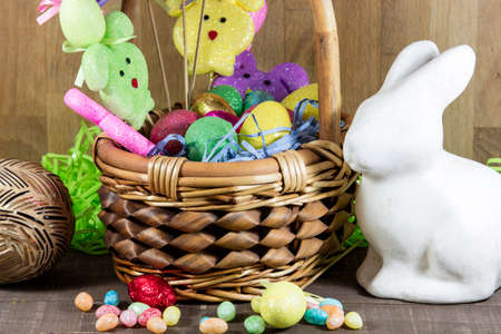 Easter basket filled with colored eggs and bunnies, with candy on table top