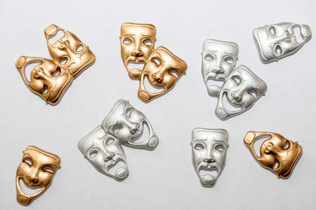 drama masks: Small Greek drama masks in gold and silver on white backgroun Stock Photo