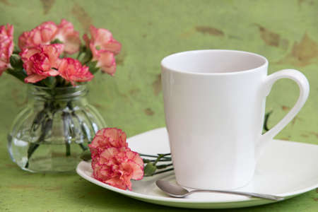 Small bouquet of Carnations set by a cup of tea