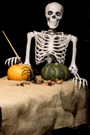 terrifying: Halloween skeleton holding a brush and painting pumpkins and decorations for the celebration