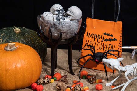 Table full of Halloween treats and decoration with spiders, skeletons and pumpkins