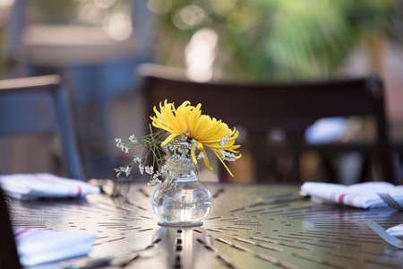 Table setting at a restaurant patio with yellow flower in a vase