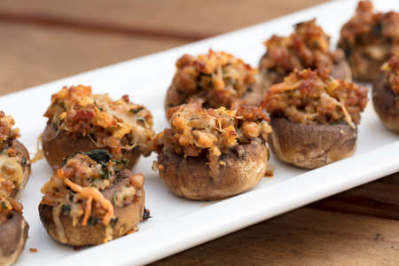 Sausage and Cheese baked stuffed mushrooms plated on white ceramic on a wood table