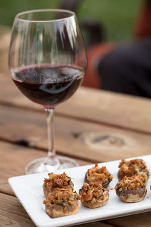 Sausage and Cheese baked stuffed mushrooms plated on white ceramic on a wood table and glass of wine
