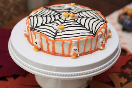 hallowen: White frosting Hallowen cake with orange and black icing and candy ghosts Stock Photo