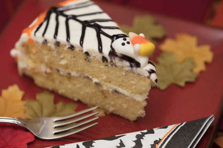 White frosting Hallowen cake with orange and black icing and candy ghosts, served on a red plate with fork