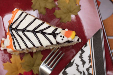 hallowen: White frosting Hallowen cake with orange and black icing and candy ghosts, served on a red plate with fork