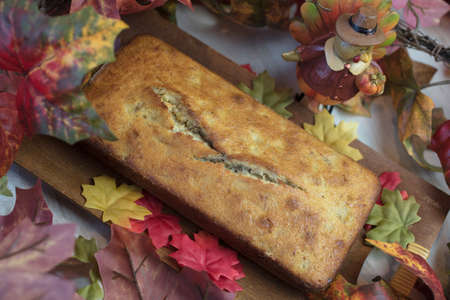 banana bread: Thanksgiving banana bread plated on a wood tray surrounded by autumn leaves and a turkey decoration