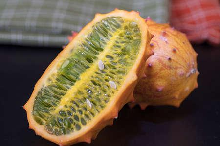Dos Frutas Kiwano naranja y verde fijados sobre una mesa con la piel espinosa