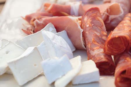 A plate of salami, sopressata, pepperoni,  cheddar and brie cheeses for an outdoor get together Stock Photo