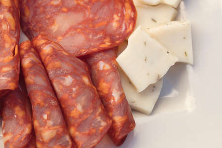 A plate of salami, sopressata, pepperoni,  cheddar and brie cheeses for an outdoor get together Banco de Imagens