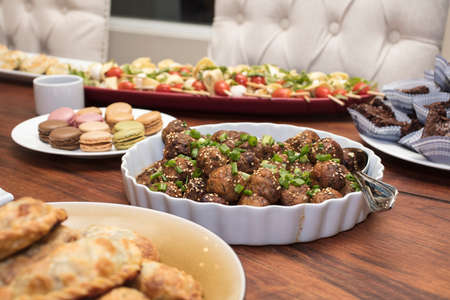 Appetizers dishes with meatballs, empanadas, macarrons, tomatoes, pasta and brownies
