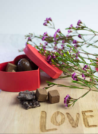 Box of chocolate candy and flower on a cutting board marked with the word Love for Valentines Day Stock Photo