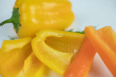 Yellow and orange mini peppers on a plate, sliced to be used as an ingredient