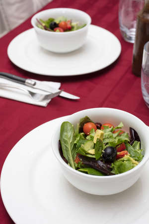 Green Salad with Lettuce, Tomato, Avocado and Olives served in White Dinnerware and Red Table Cloth