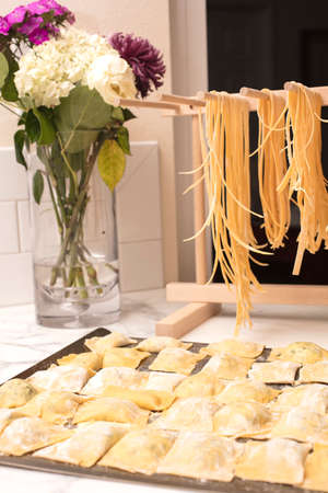Homemade Spaghetti Drying on a Pasta Rack and Ravioli Ready to be cooked