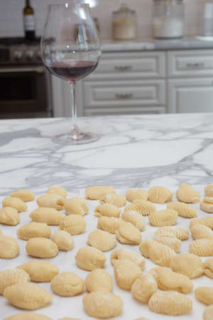 Homemade Gnocchis on a kitchen counter top ready to be cooked with a glass of wine Banco de Imagens
