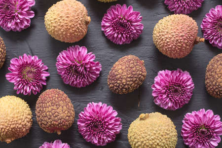 Grouping of Lychee fruit and purple garden mums laid on a slate cutting board