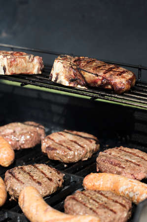 Hamburgers, steaks and sausages being grilled on an outdor barbecue Banco de Imagens
