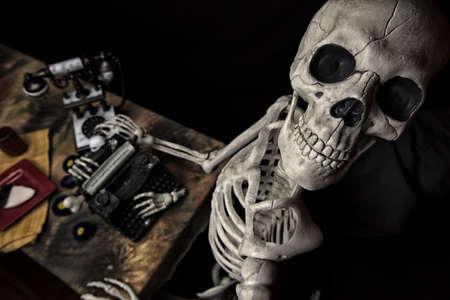 타자기, 전화 및 접시에 쿠키와 인간의 할로윈 해골 스톡 콘텐츠