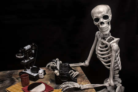 Human Halloween Skeleton with a Typewriter, Telephone and Cookie On A Plate