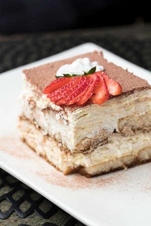 Tiramisu made with chocolate and layers of cake and cream, topped with strawberries