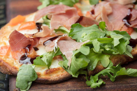 Prosciutto, arugula and cheese flatbread dish baked until crispy and browned