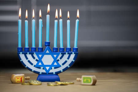 Hanukkah candles lit for the holiday celebration surrounded by dreidels and chocolate coins Archivio Fotografico