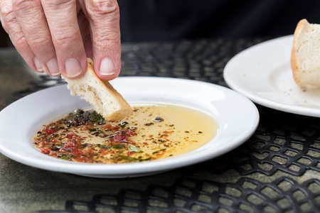 Person bread dipping in a seasoned olive oil on a white plate Banco de Imagens