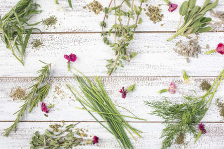 Tarragon, Rosemary, Chives, Sage, Marjoram and Dill herbs on a rustic table top with edible flowers