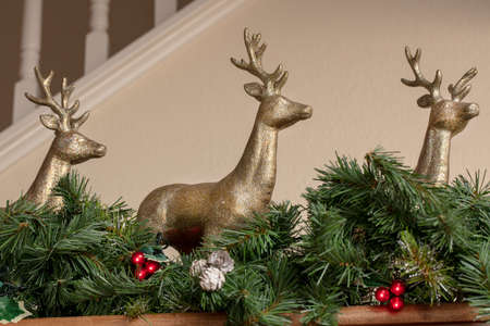 Three golden reindeer Christmas decorations on a mantel with green garland