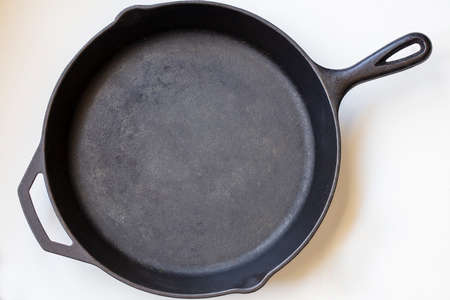 Black iron handled skillet on a white background on a diagonal