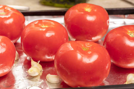 Tomatoes and garlic being prepared with oil and spices for roastin in an oven on a sheet pan Stock Photo