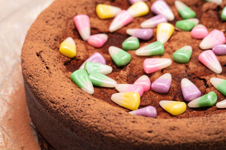 Flourless dark chocolate cake with pastel colored candy corn on top on a clear serving plate