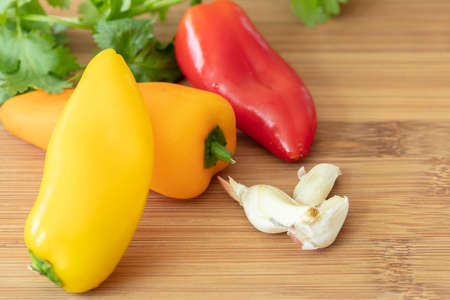 Chopping board with yellow, red and orange bell mini peppers, garlic cloves and parsley