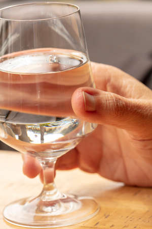 Hand of a person holding a wine glass of water in a restaurant